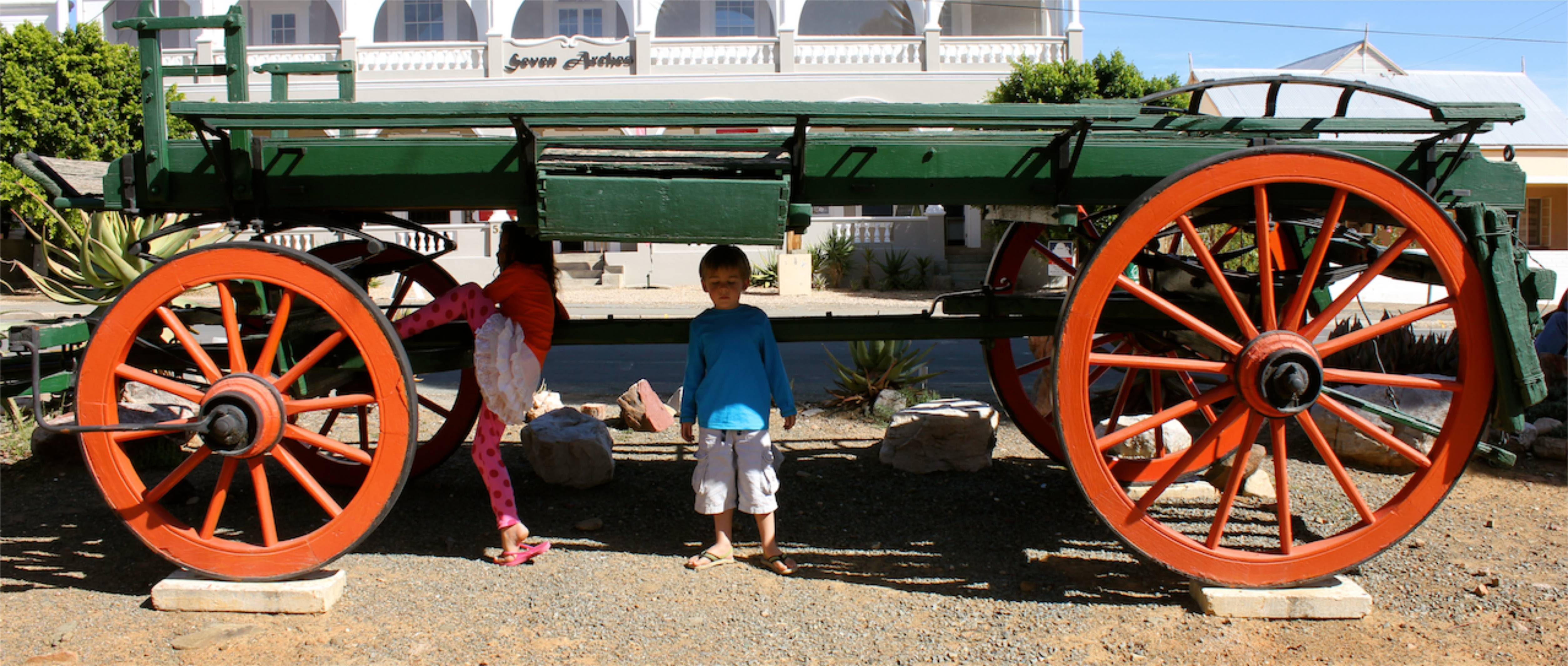 The kids exploring an old wagon outside the Fransie Pienaar Museum...