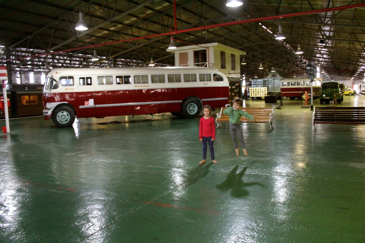 Kids jumping in front of an old bus...