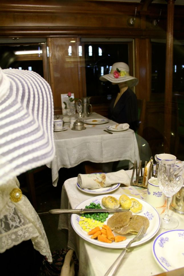 Mannequin ladies in floppy hats enjoying their meals...