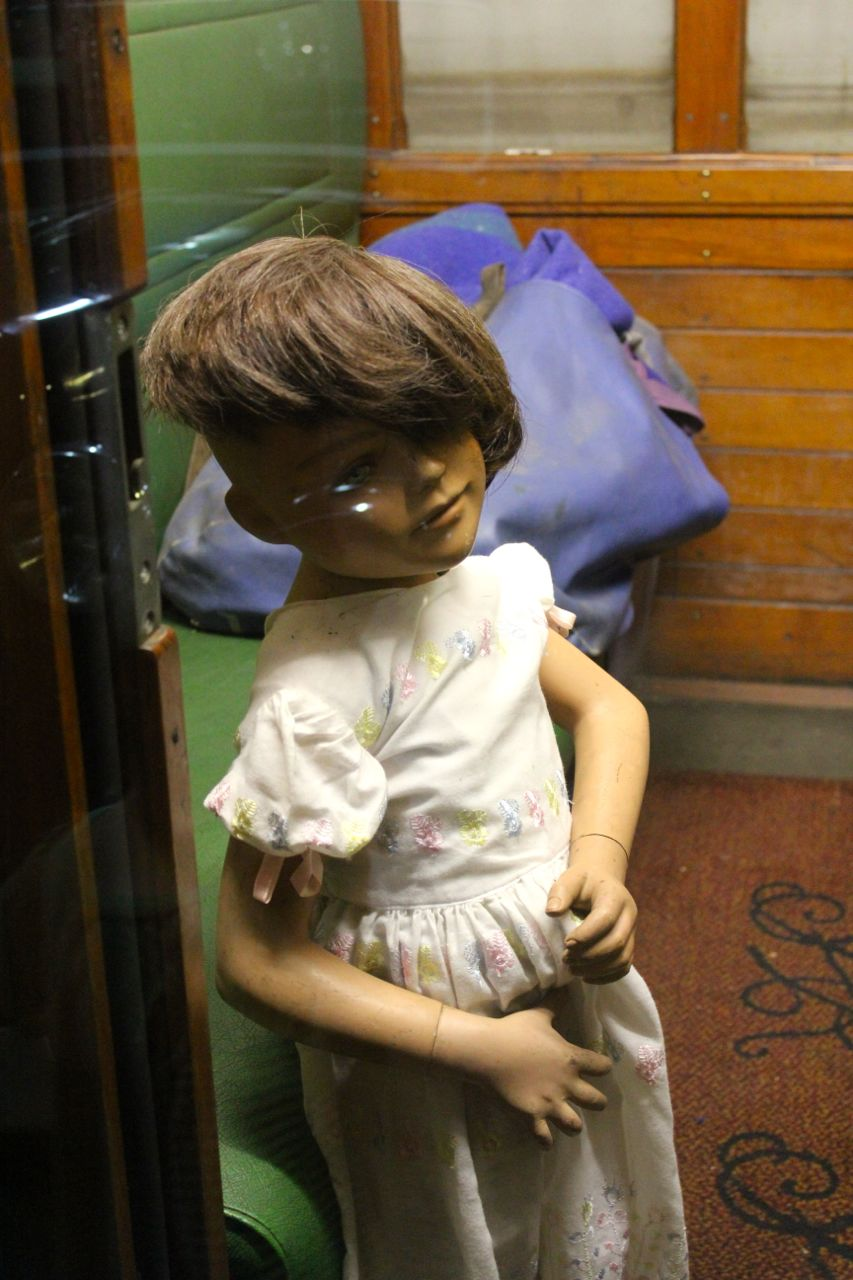 Mannequin-child with unfortunate hair enjoying the view from her private compartment...