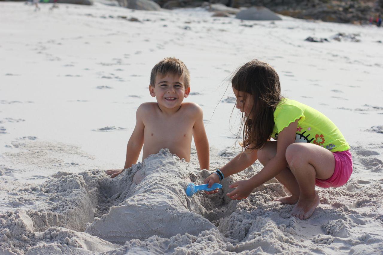 Gabi making a sand mermaid tail for Joah...