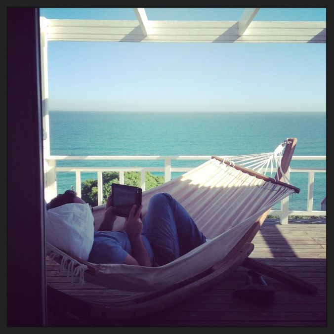 Nick working (reading a script for the next film) on the hammock at the Misty Cliffs beach house...